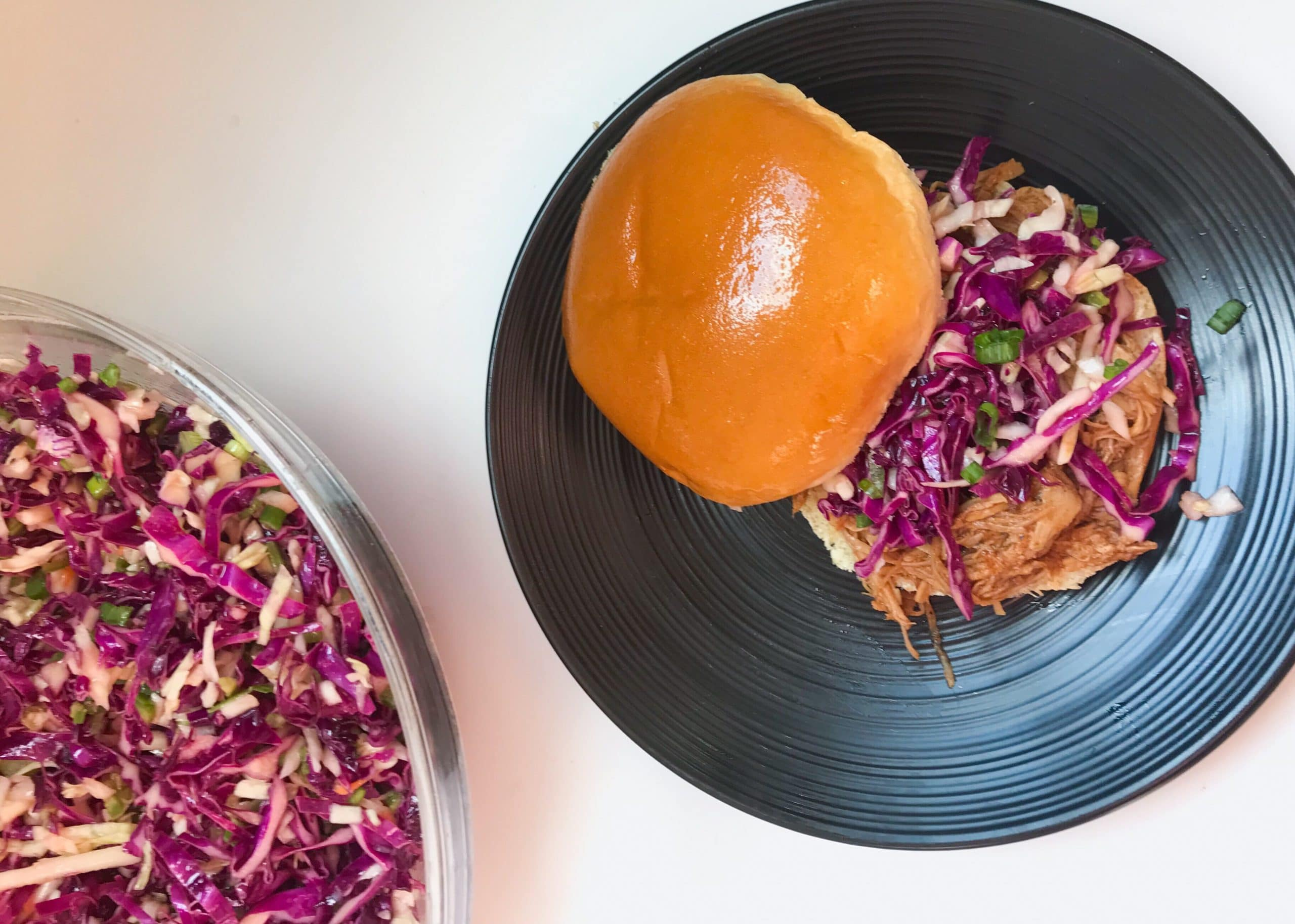 The Instant Pot turns the pork roast into juicy pulled pork far faster than the alternative options. The slightly spicy and crunchy Jalapeño Slaw perfectly pairs with the juiciness and sweetness of the barbecue pulled pork. The recipe includes slow cooker instructions. Recipe at KathleensCravings.Com. #InstantPot #InstantPotPulledPork #JalapenoSlaw #SummerEats #CookoutFood #CrowdPleasingFood #Sliders #SlowCooker