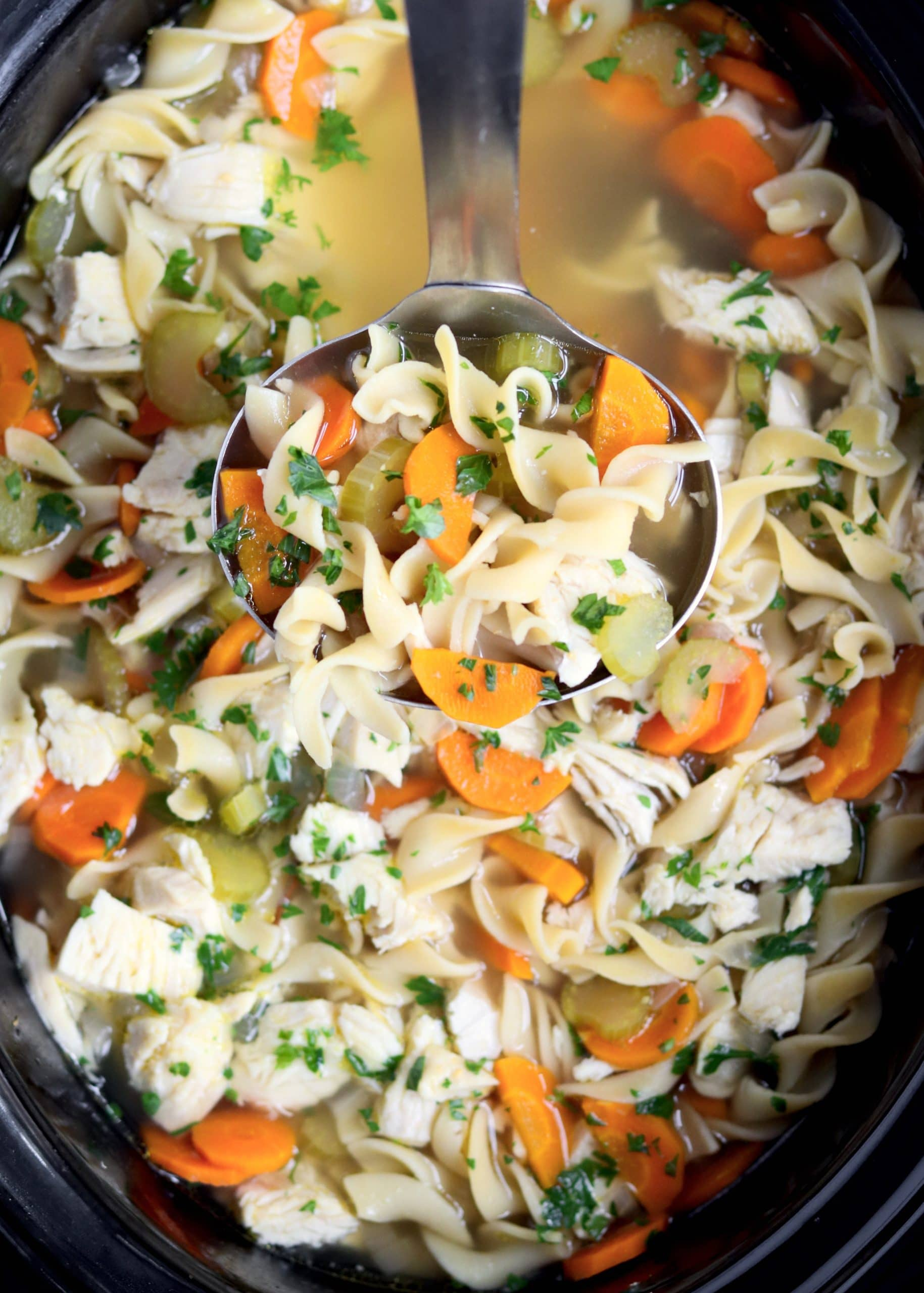 Ladle of chicken noodle soup in crockpot