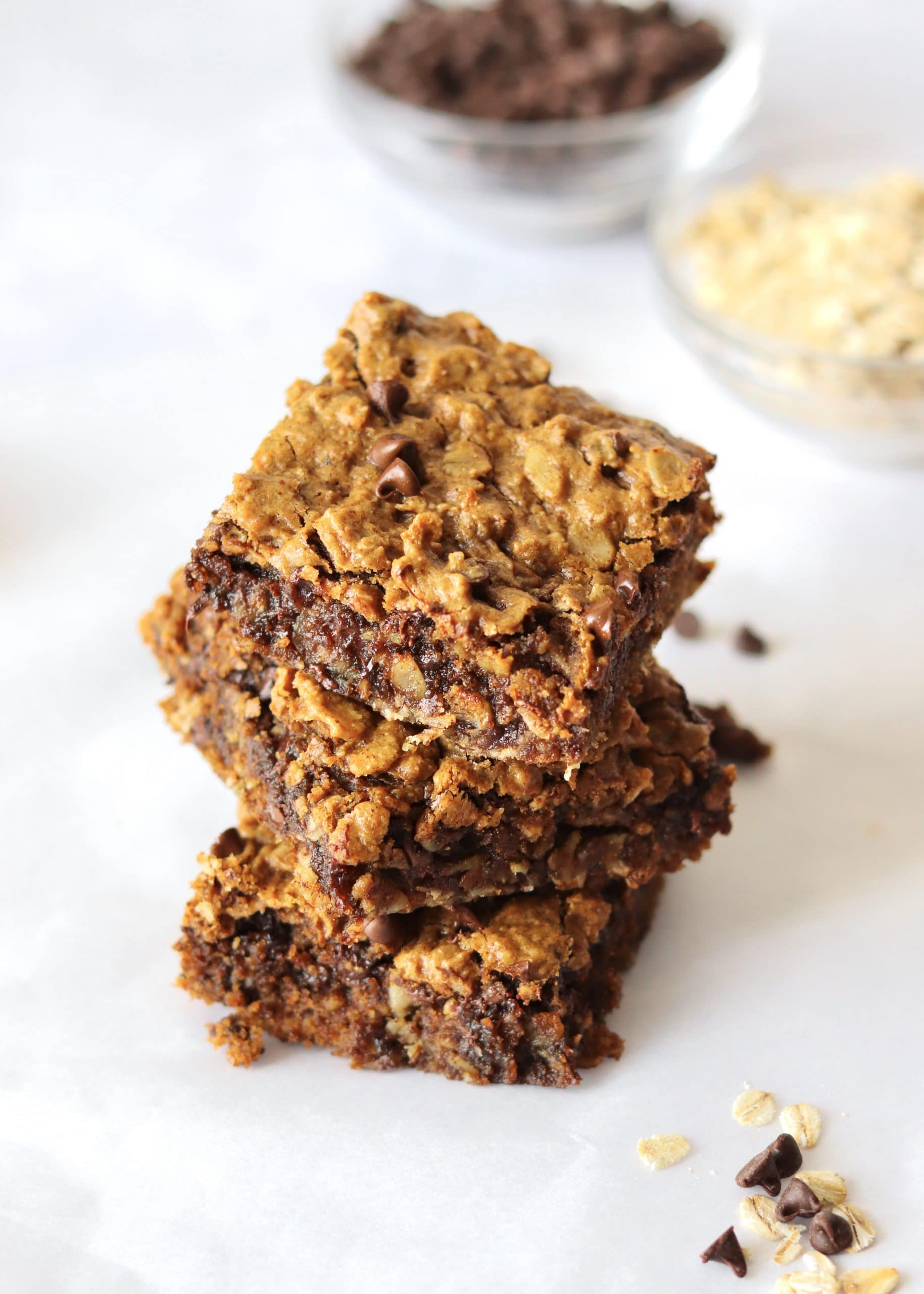 Stack of oatmeal cookie bars with bowl of oats