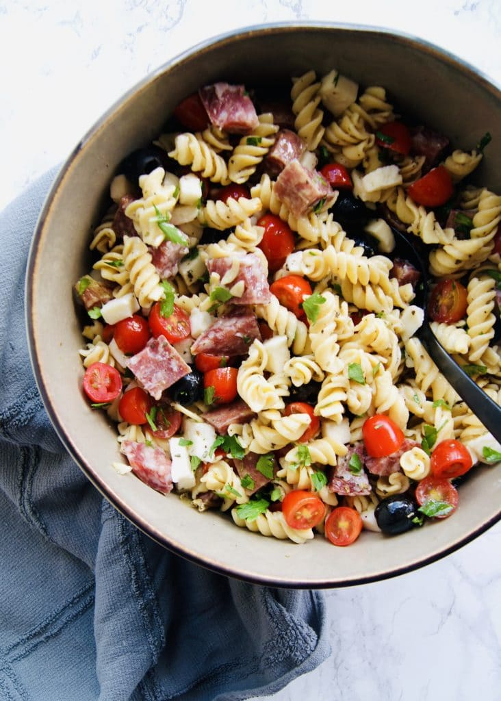 pasta, olive, mozzarella, salami, tomatoes, and parsley mixed together in a bowl