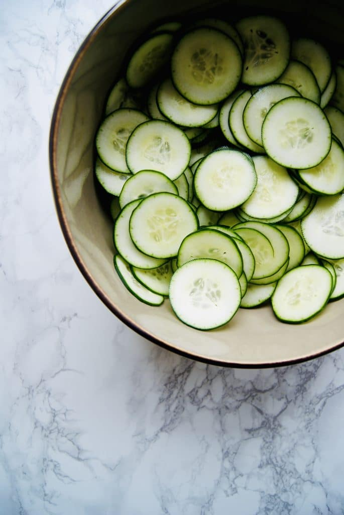 Thinly sliced cucumber rounds in a bowl