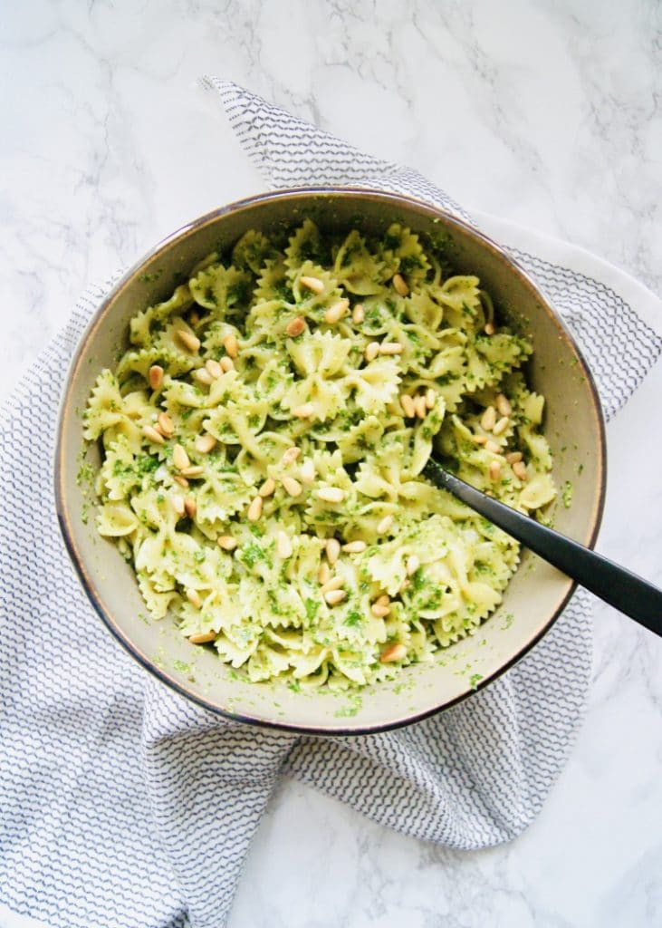 Bowtie pasta tossed with parsley pesto in a large bowl