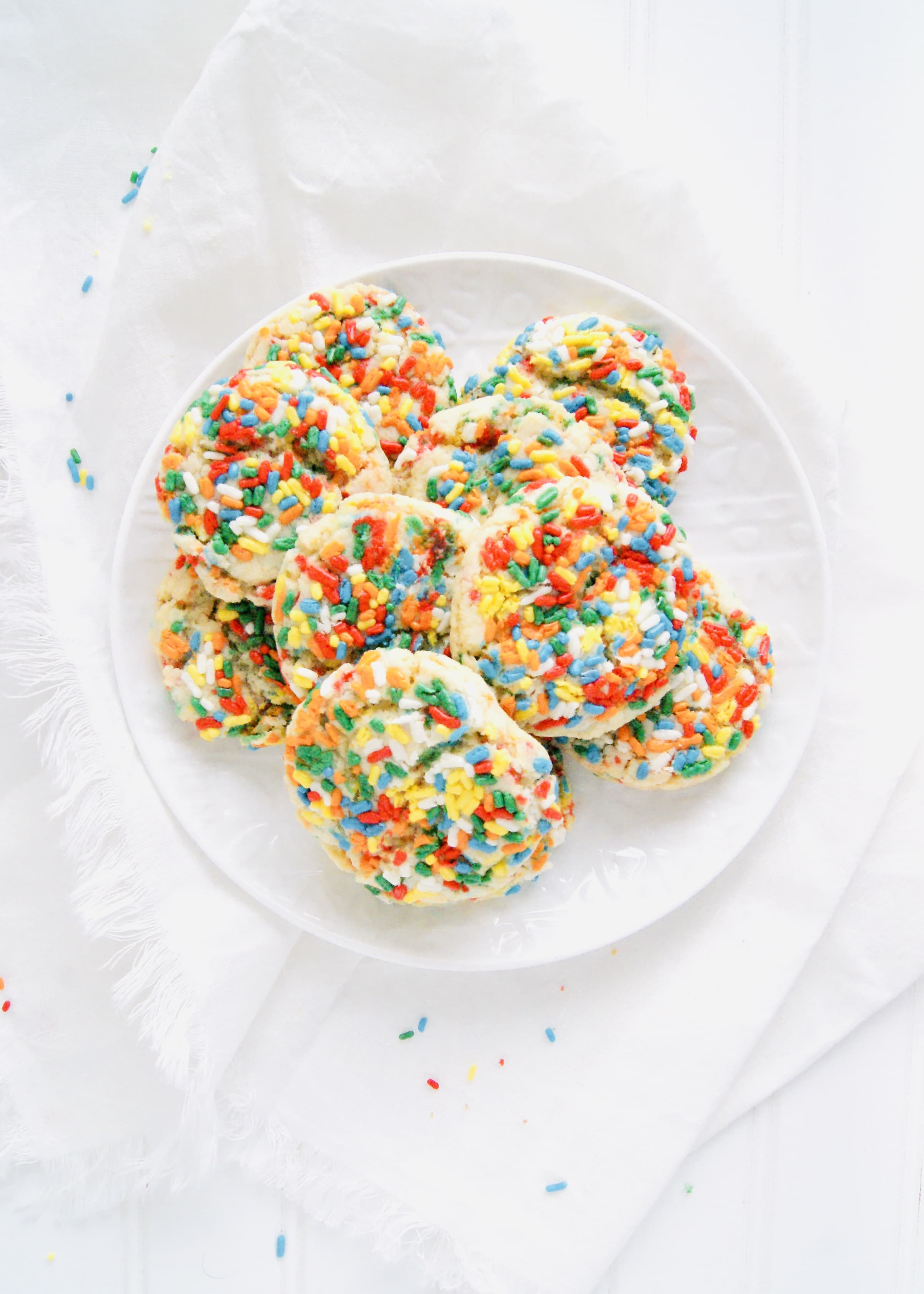 Drop Sugar Cookies that are soft, chewy and filled with lots of sprinkles. No rolling or cutting. Just roll the simple cookie dough into balls and bake. Recipe at KathleensCravings.com #sugarcookies #dropsugarcookies #holidaycookies #christmascookies #baking #holidaybaking #easysugarcookies #sprinkles
