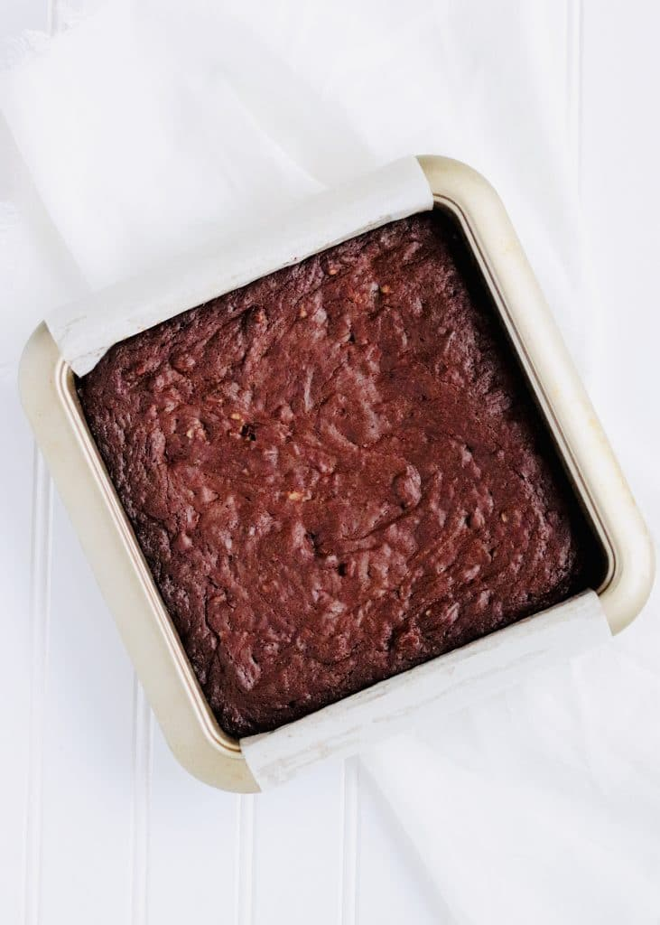 Fudgy brownies in pan with parchment paper