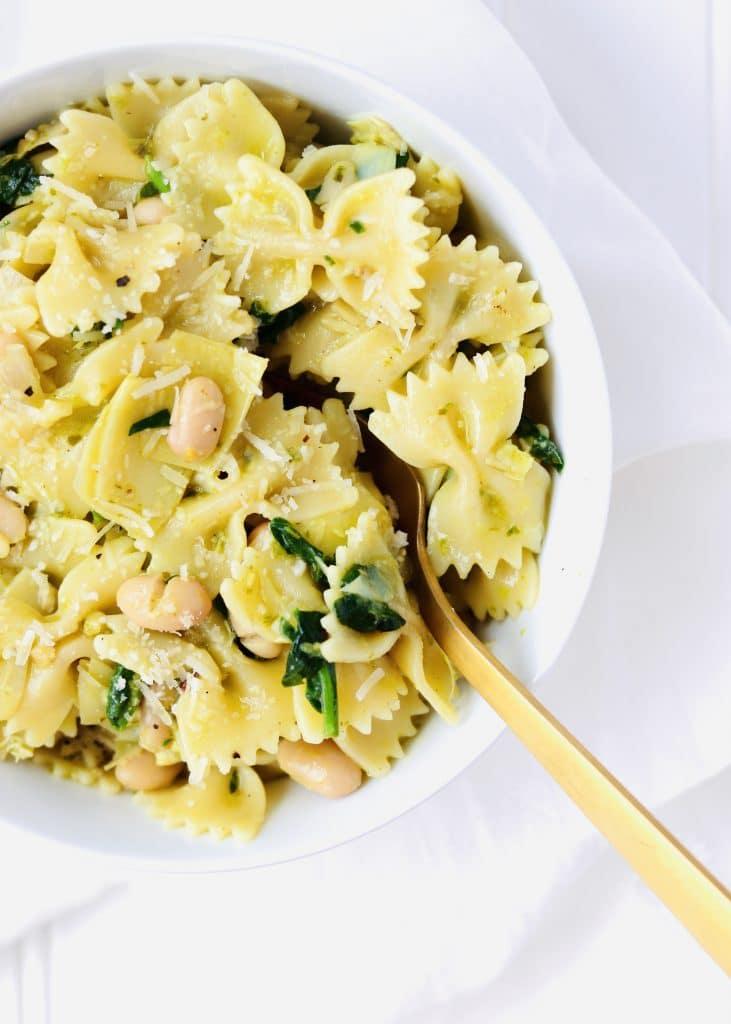 Spinach Artichoke Pesto Pasta in bowl with fork