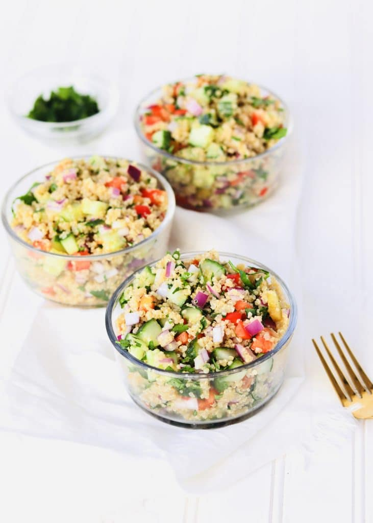 Quinoa salad in bowls with fork and parsley