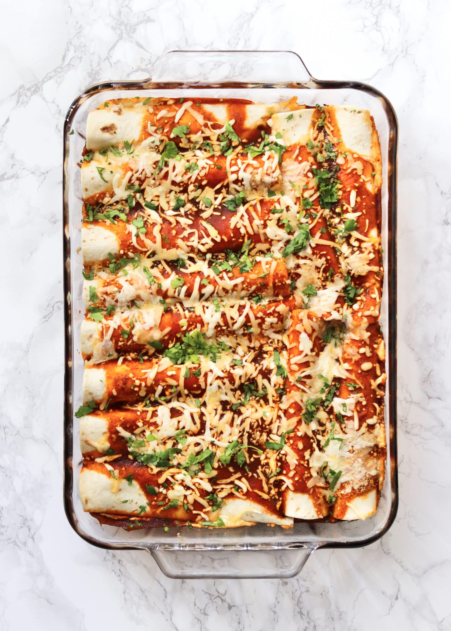 Baked cheesy vegetarian enchiladas in glass dish