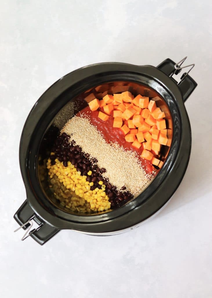 Corn, black beans, quinoa, tomato sauce, and sweet potatoes in a crock pot