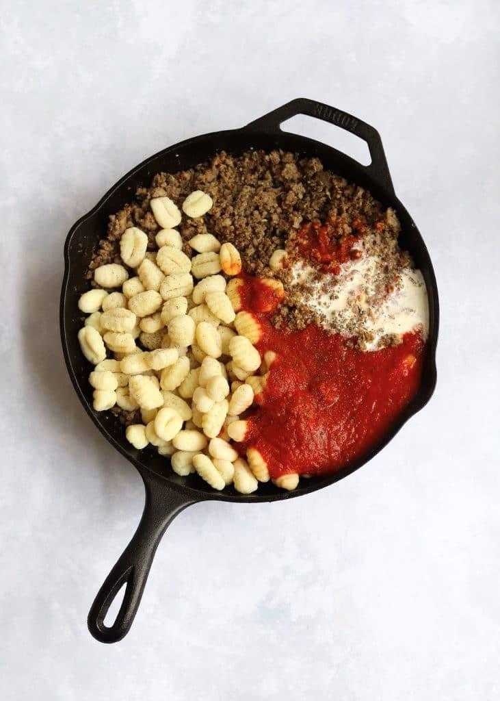 Gnocchi, Italian sausage, marinara, and cream in a cast iron skillet