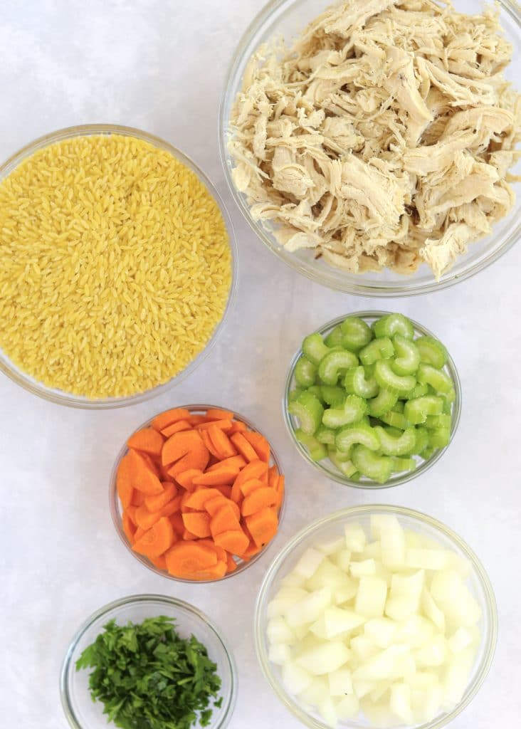 Shredded chicken, orzo, celery, carrots, onion, and parsley in glass prep bowls