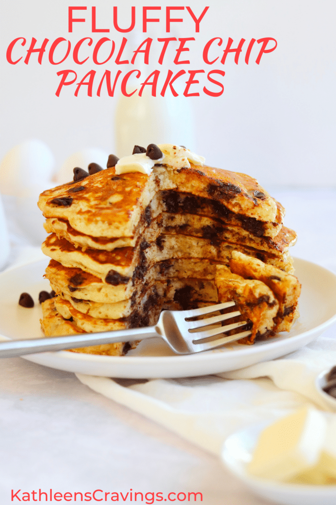 Stack of chocolate chip pancakes with a bite cut out on a fork