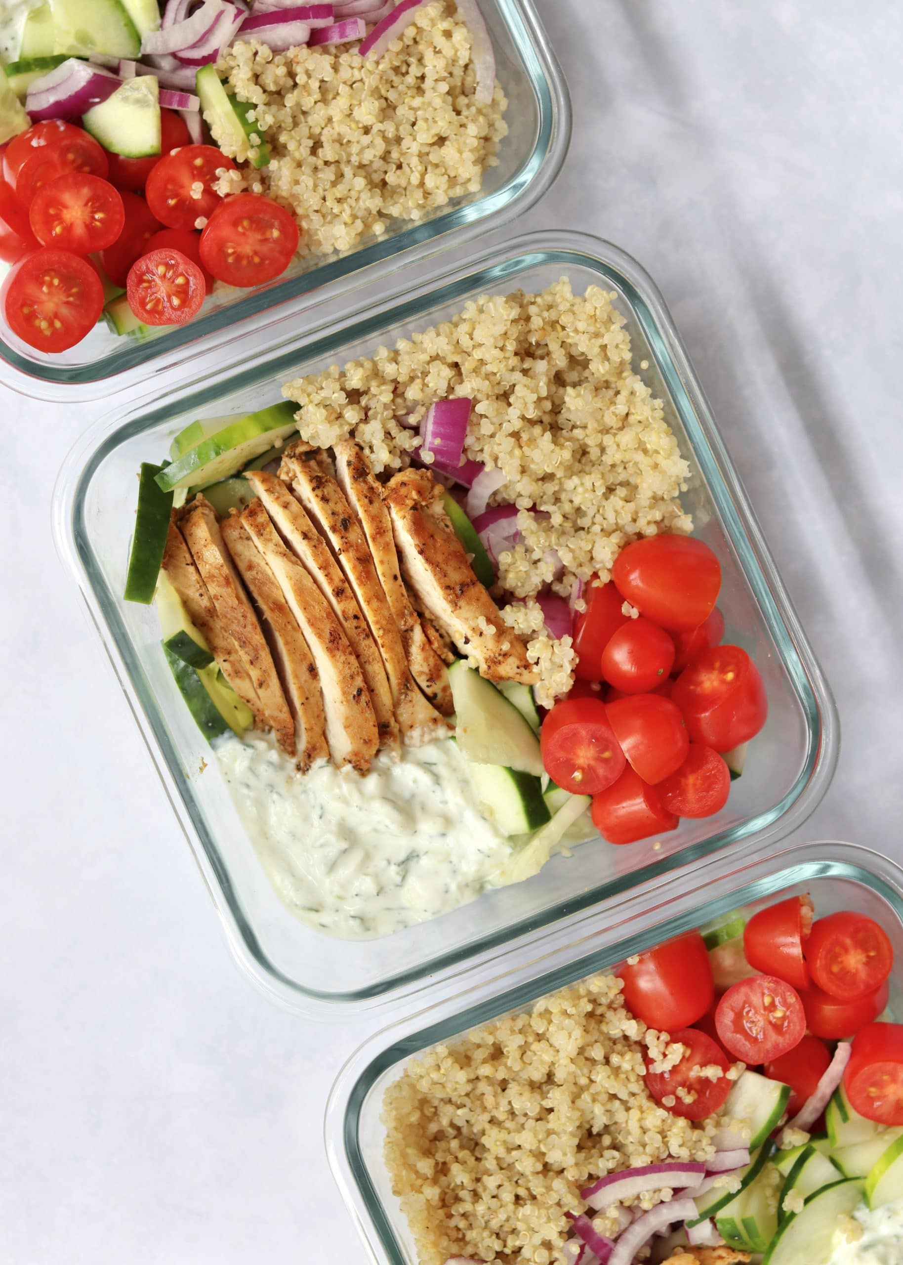 Greek chicken, quinoa, tzatziki, and veggie in meal prep containers