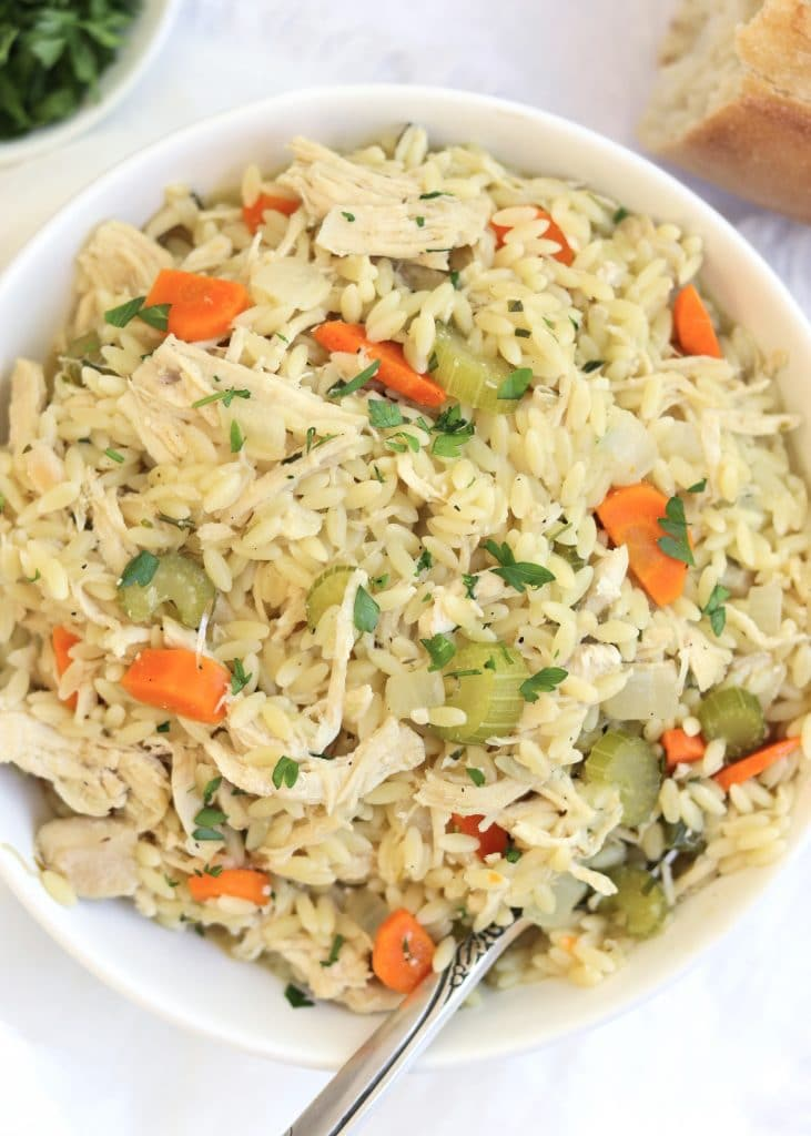chicken orzo in a bowl with crusty bread and parsley