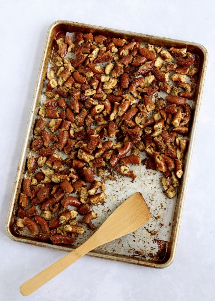 Spicy seasoned pretzels on sheet pan with wooden spoon
