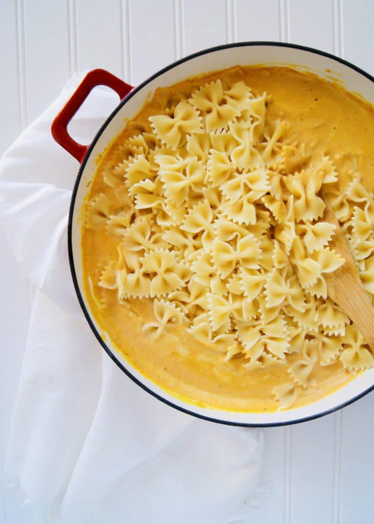 Bow tie pasta being stirred into the pumpkin sauce