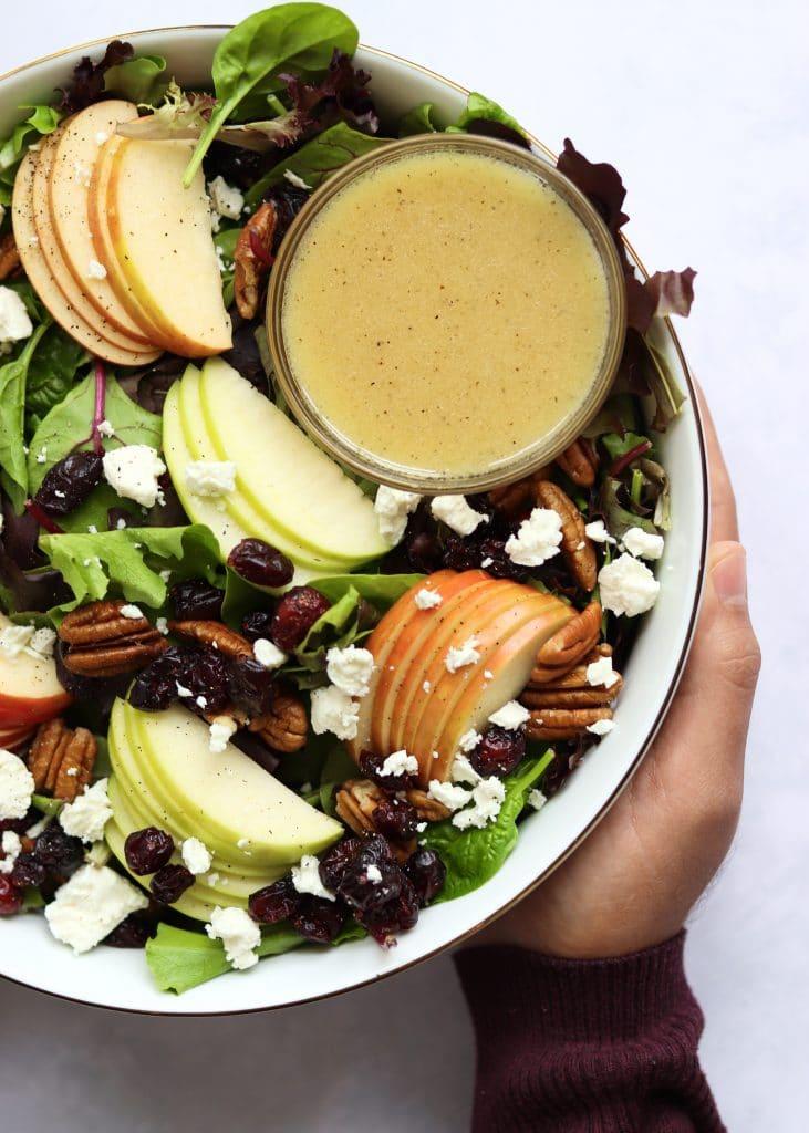 Close up shot of harvest salad in large bowl with apple cider vinaigrette dressing
