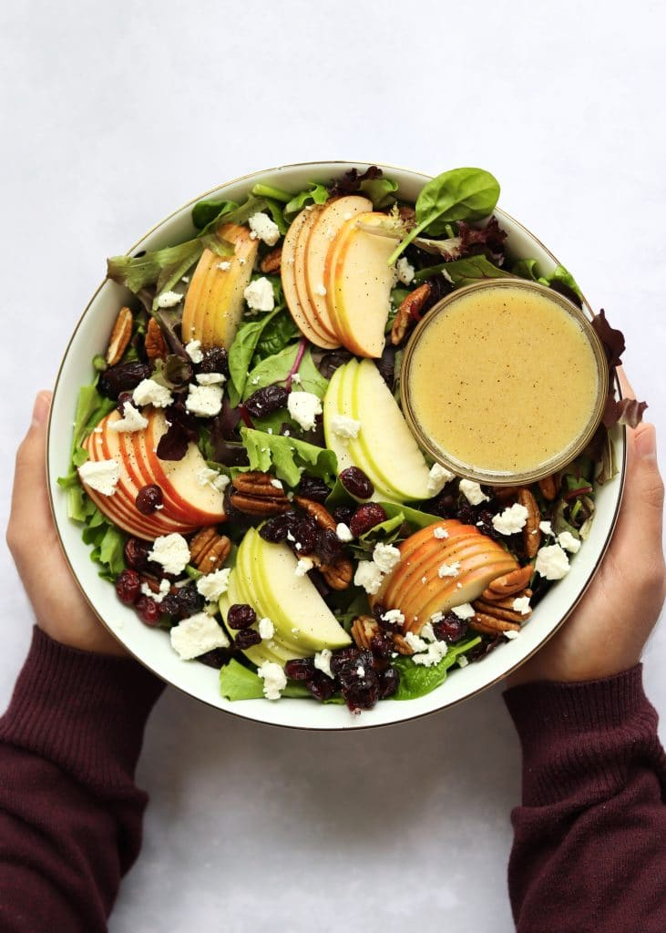 Hands holding bowl of apple pecan salad with crumbled goat cheese