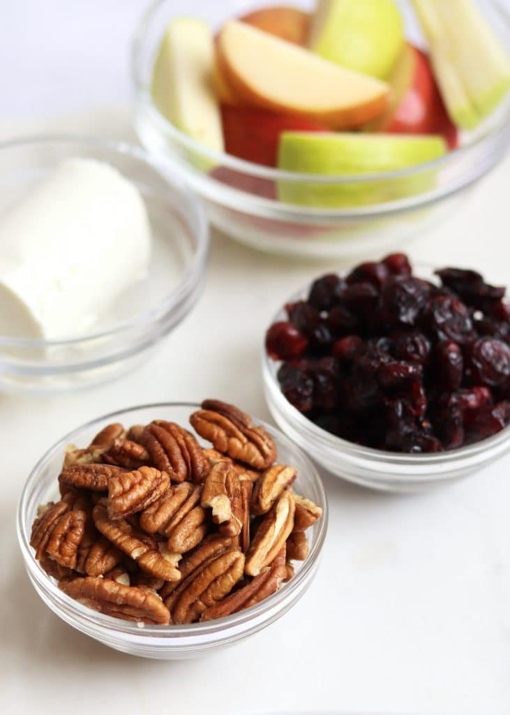 Pecans, dried cranberries, goat cheese, and sliced apples in glass bowls
