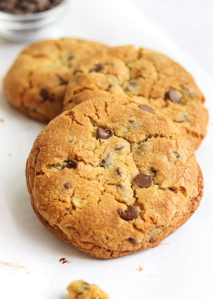 three giant cookies with small bowl of chocolate chips