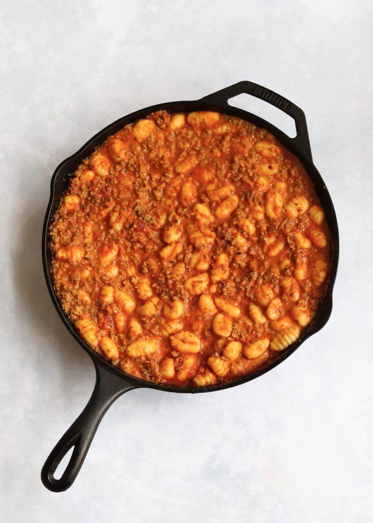 Gnocchi mixed with sausage and marinara in skillet