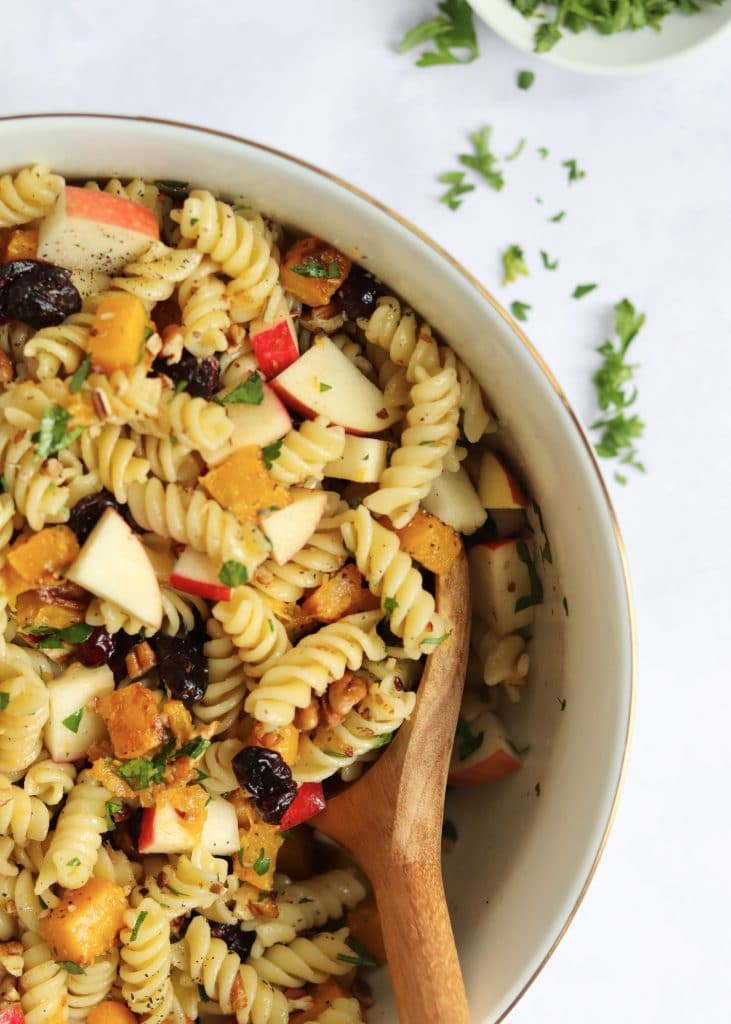 Tossed vegan pasta salad in a large bowl with fresh parsley