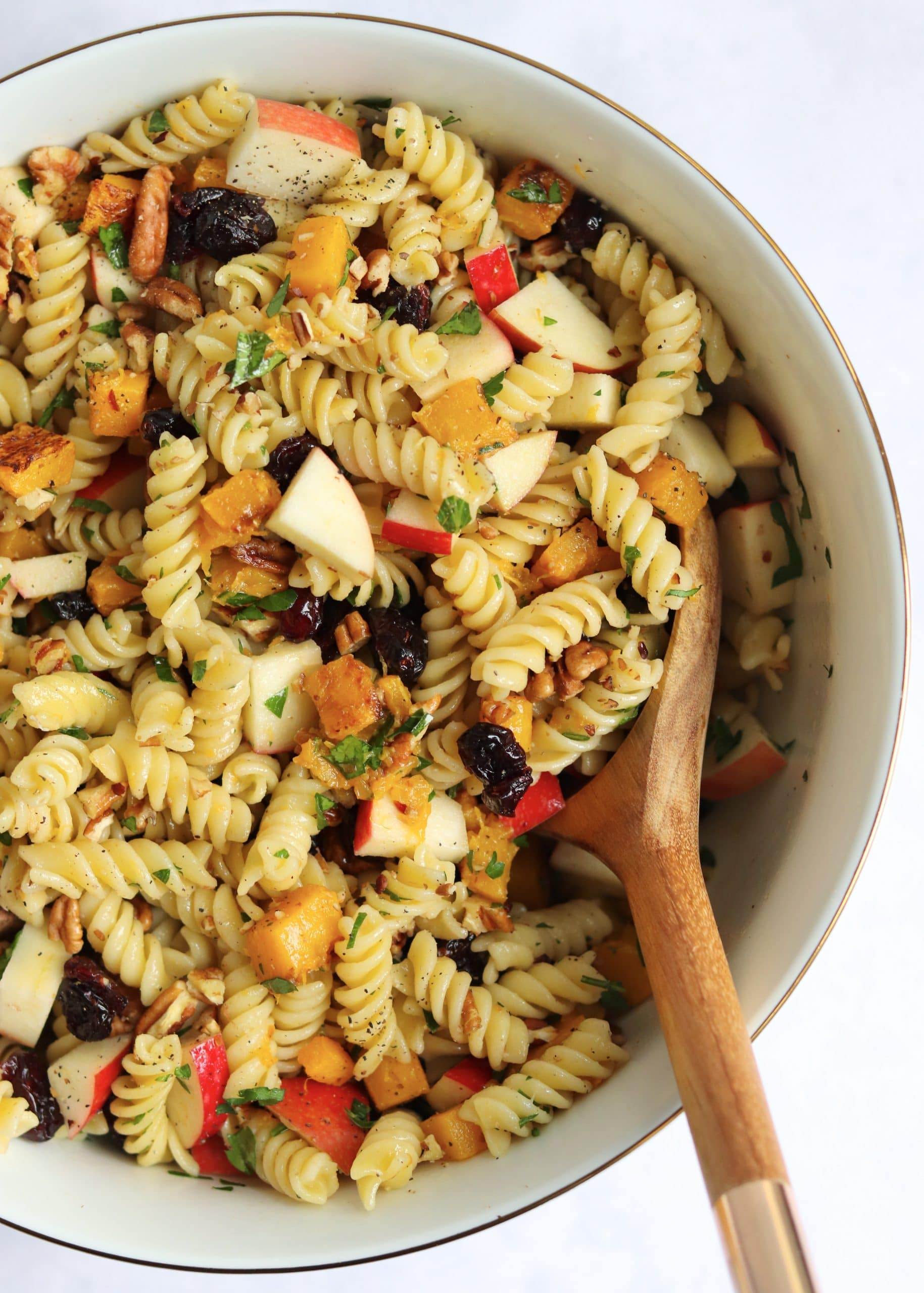 Wooden spoon in bowl of vegan pasta salad