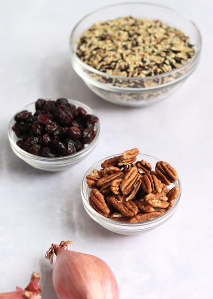 Shallots, pecans, dried cranberries, and a wild rice blend in glass bowls