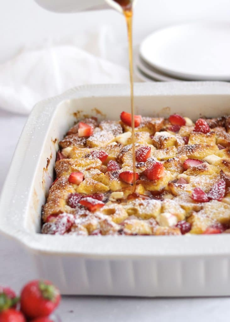 Maple syrup being poured onto French toast casserole