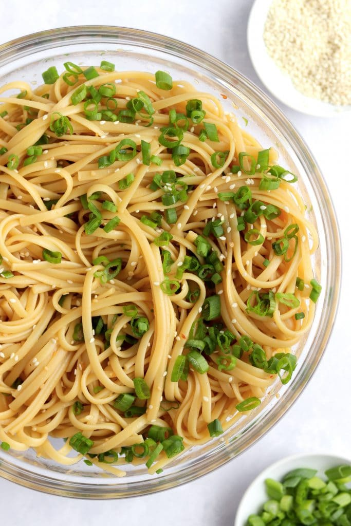 Bowl of sesame noodles with sliced green onions and sesame seeds