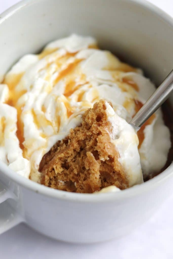 Close up of spoon of gingerbread mug cake with whipped cream and caramel