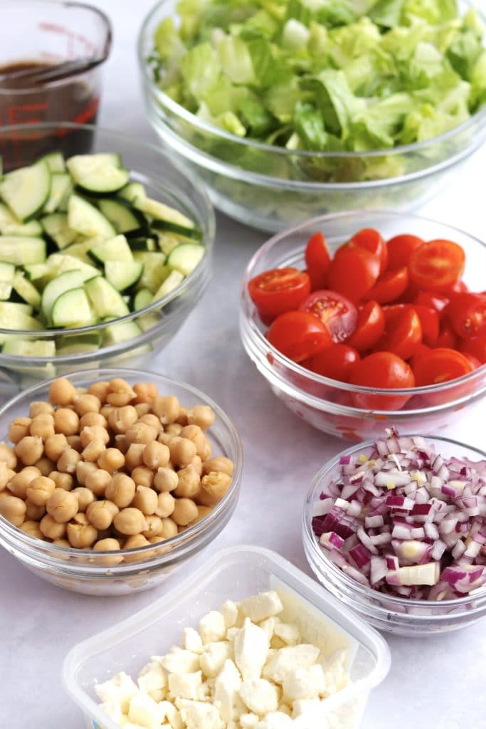 Salad ingredients in bowls - feta, chickpeas, red onion, tomatoes, cucumber, lettuce, and greek dressing