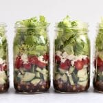 four greek salads in mason jars