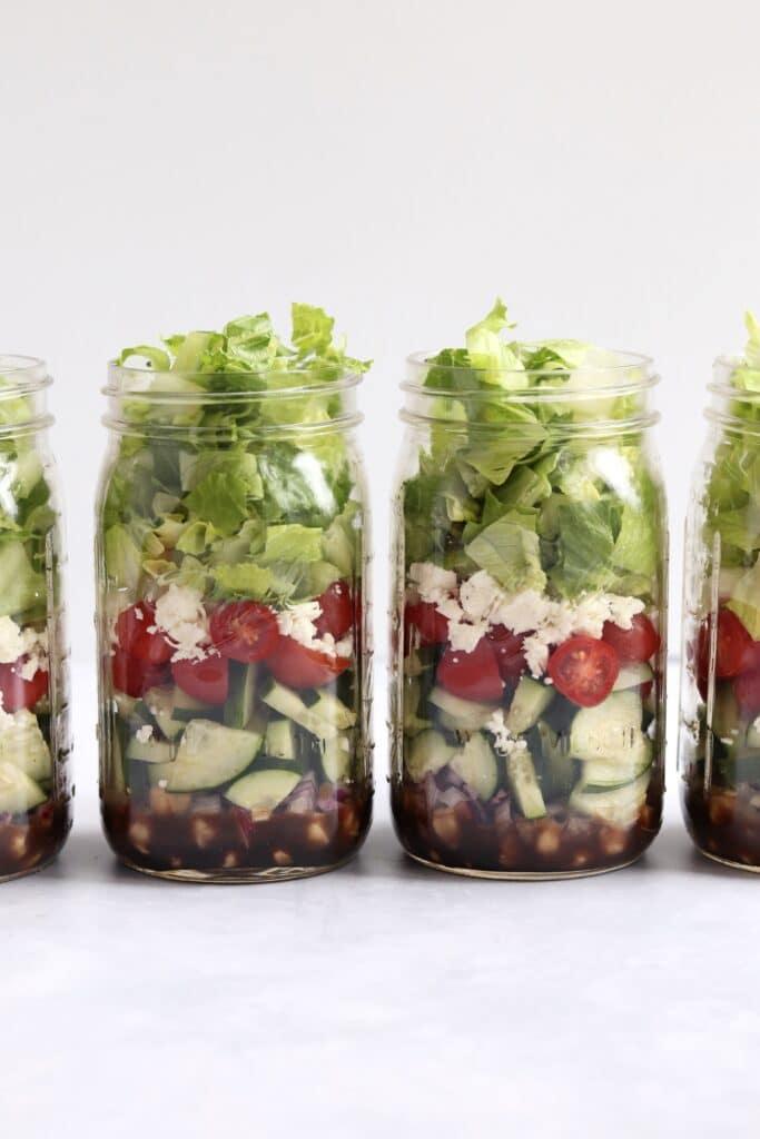 four greek salads in jars