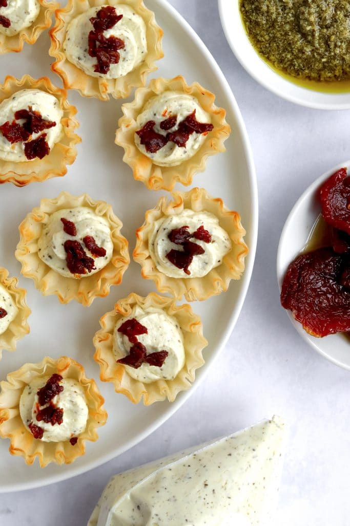 Feta cream cheese filling in a piping bag with phyllo cups and sun dried tomato