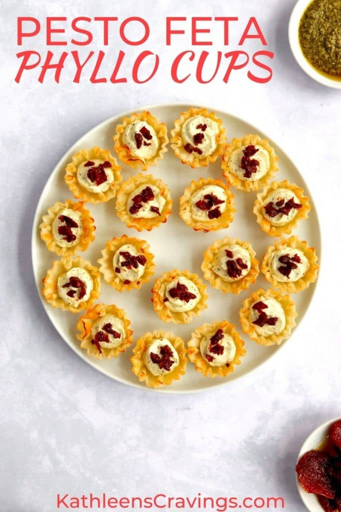 Plate of feta cream cheese phyllo cup appetizers with pesto and sun dried tomatoes