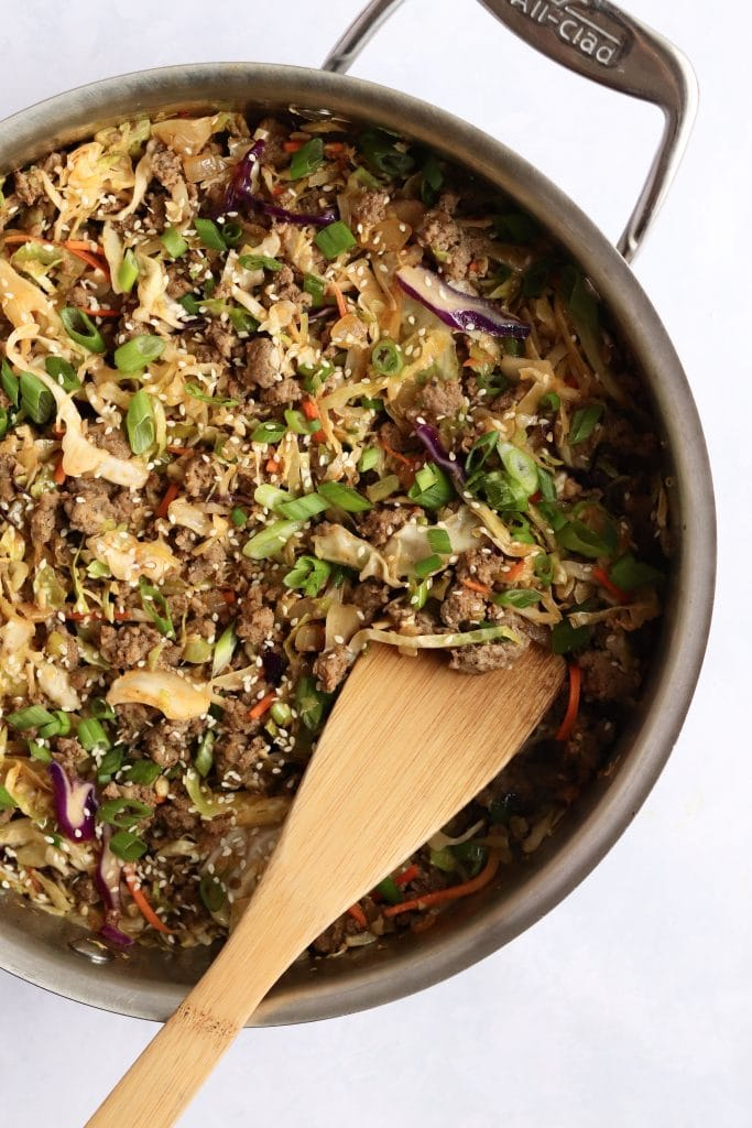 Pork egg roll bowl in a large pan with a wooden spatula