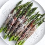 Prosciutto wrapped asparagus with parmesan on a plate