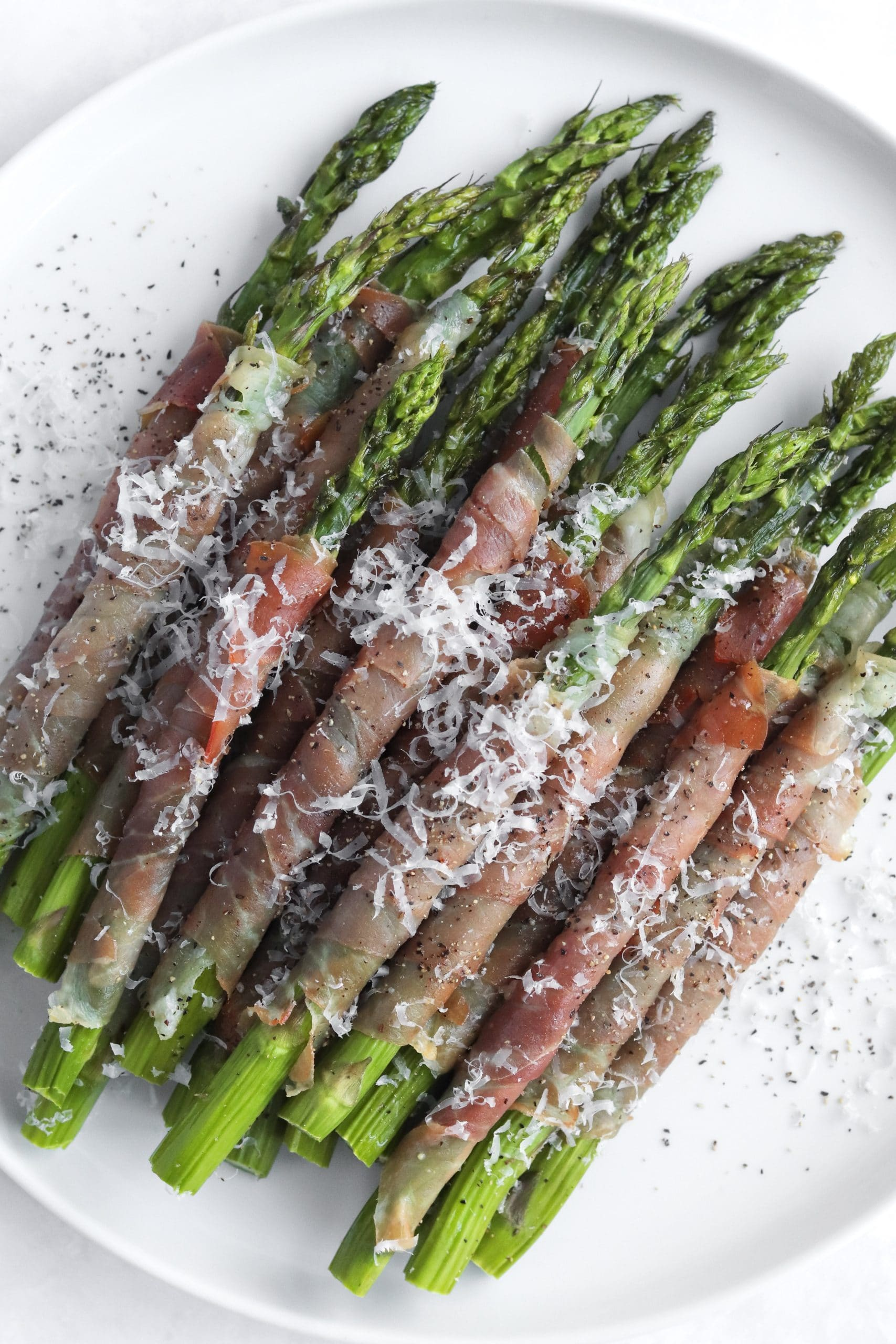 Prosciutto wrapped asparagus on a plate with parmesan cheese