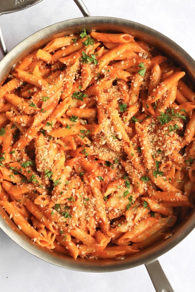 Vegan creamy tomato pasta sauce tossed with penne in a large pan