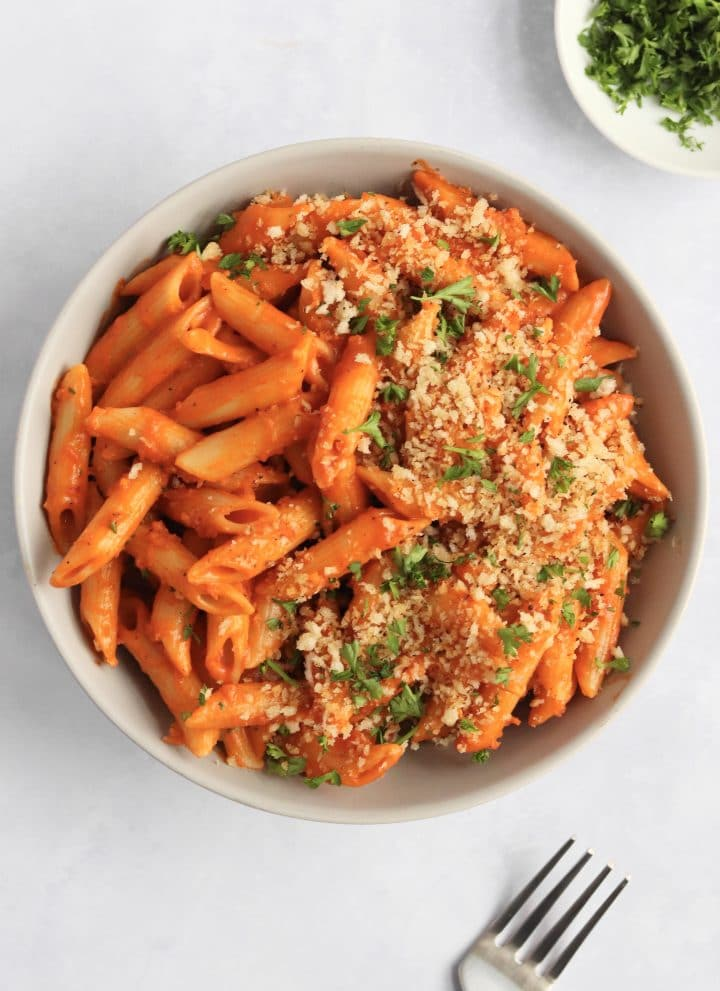 bowl of vegan creamy tomato pasta with bread crumbs