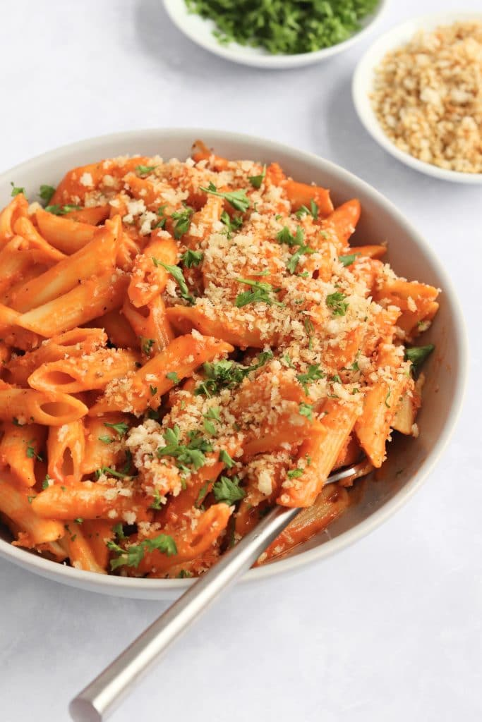 Vegan creamy tomato pasta made with coconut milk and topped with breadcrumbs