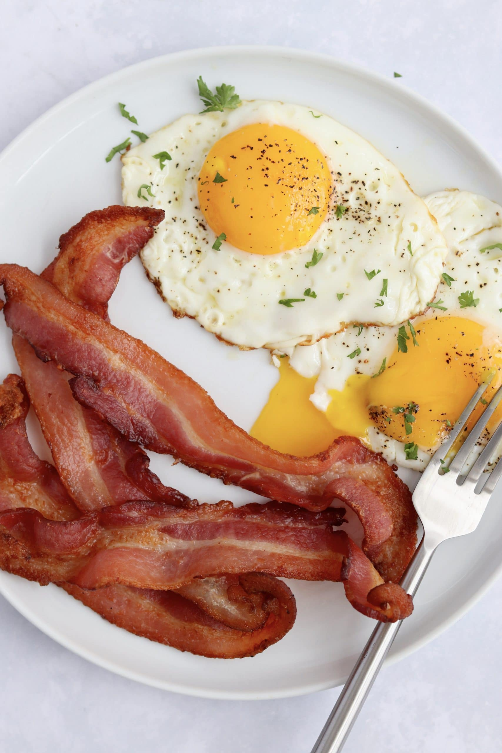 crispy air fryer bacon and sunny side up eggs on a plate