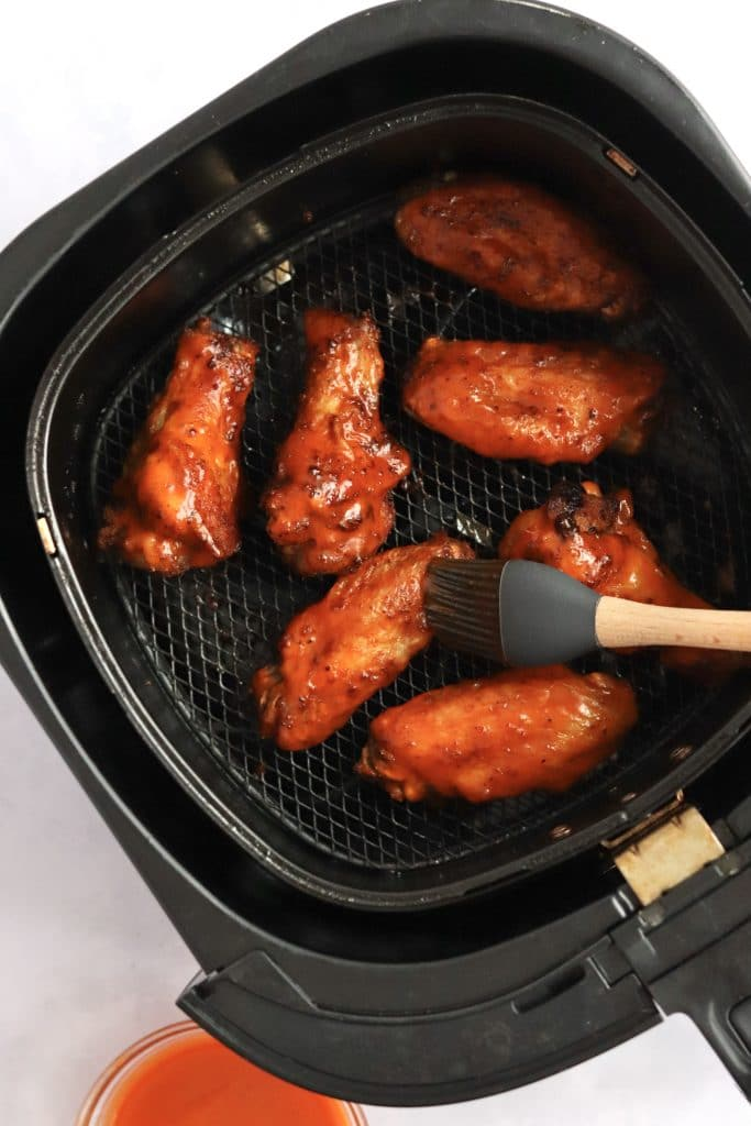 Chicken wings in an air fryer being brushed with buffalo sauce