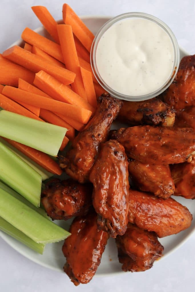 air fryer buffalo chicken wings, carrots, celery, and ranch dressing on a plate
