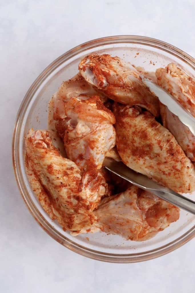Raw chicken wings toss in spices in a glass bowl with tongs