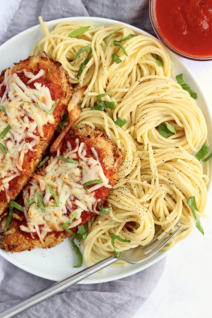 Plate of chicken parmesan with pasta and marinara