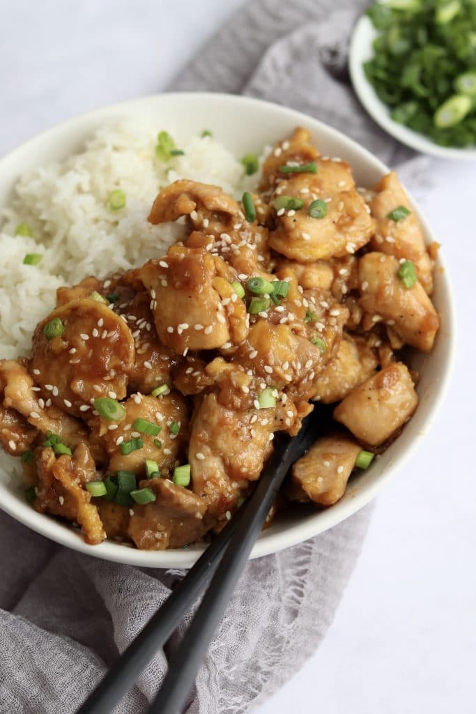 Sesame chicken with white rice in a bowl with chopsticks