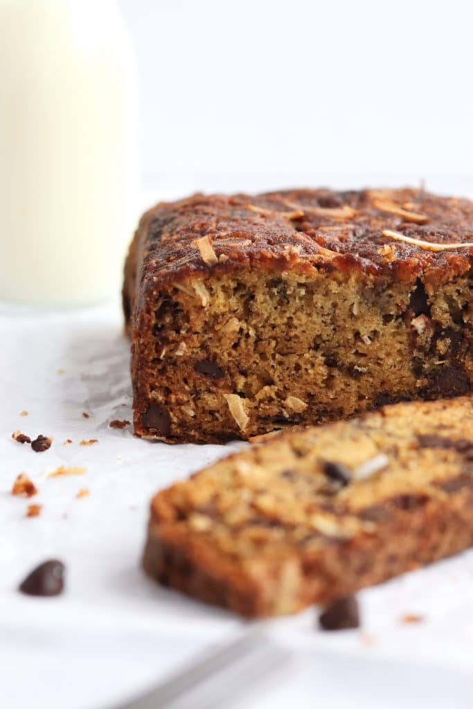 moist chocolate chip banana bread, sliced with a glass of milk
