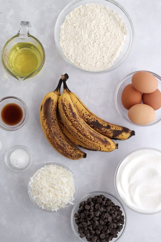 Banana bread ingredients - ripe bananas, sugar, flour, eggs, chocolate chips, coconut, vanilla extract, and oil