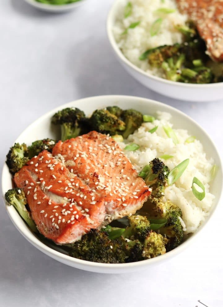 two asian salmon rice bowls with broccoli
